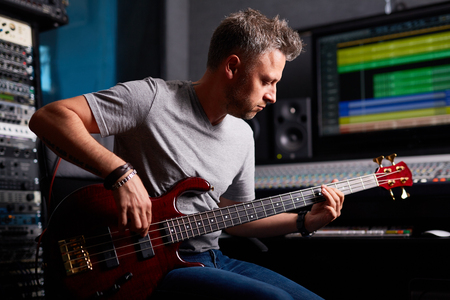 Man met gitaar zittend in audio-studio en het opnemen van zijn muziek