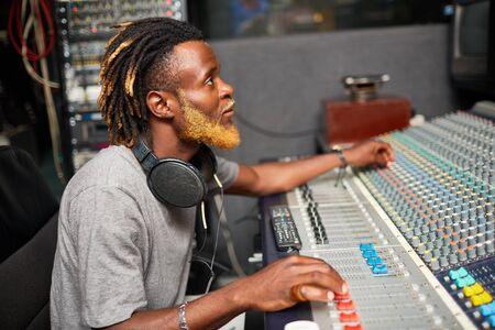 radio dj: Contemporary musician or radio dj mixing sounds in studio Stock Photo