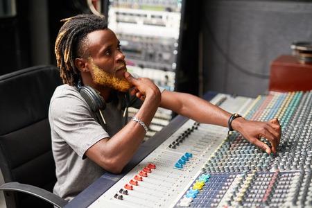 Handsome sound operator working in audio studio Stock Photo