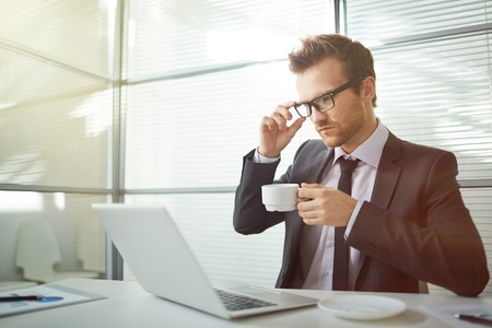 usando computadora: Young businessman drinking coffee and using computer Foto de archivo