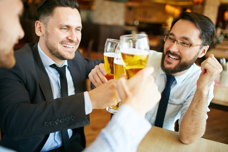 drinks after work: Businessmen celebrating and toasting with beer at pub Stock Photo