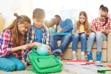 niños sentados: Los escolares sentados juntos y estudiando el mundo Foto de archivo