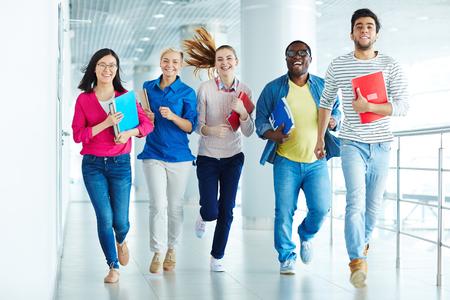 étudiants Happy courir ensemble le long du corridor
