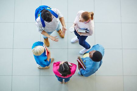 high angle view: High angle view of college students standing and communicating