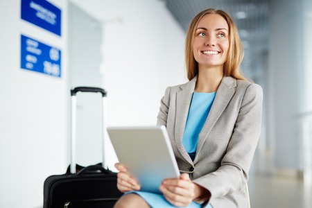 touchpad: Smiling businesswoman sitting in airport with touchpad