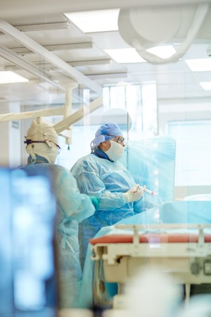 protective work wear: Surgeon in protective work wear working in operating room Stock Photo