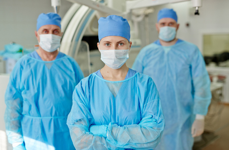 protective wear: Team of confident surgeons standing in protective wear