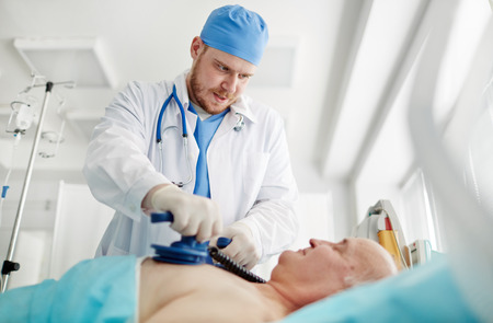 defibrillator: Doctor trying to save the patient at hospital Stock Photo