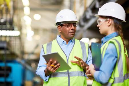 Dois engenheiros discutindo trabalho e usando o tablet pc