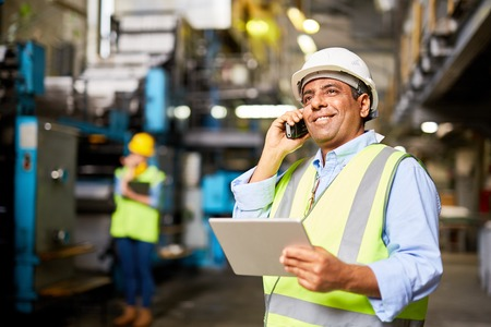 communication industry: Smiling worker with radio controlling the work process Stock Photo