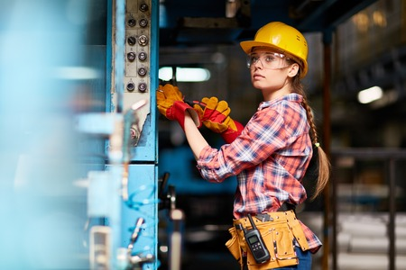 protective: Female technician in hardhat and protective eyeglasses at work Stock Photo