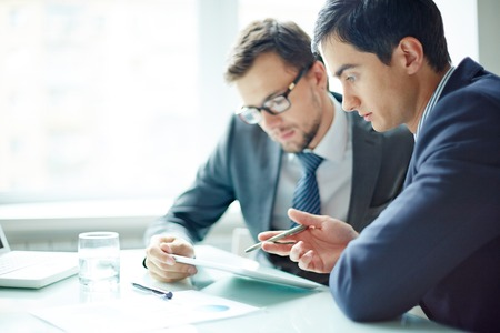 Two businessmen meeting in modern office with digital tablet photo