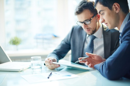 Two business partners working in team and using computer at the table photo