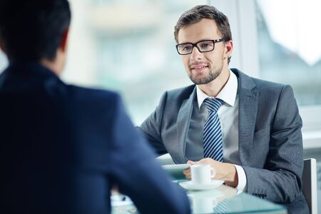 Young businessman in suit communicating with his partner at the table photo