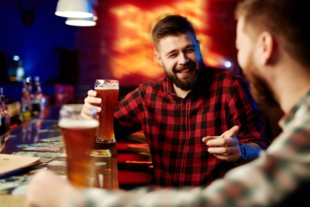 drinks after work: Man drinking beer and laughing with his friend Stock Photo