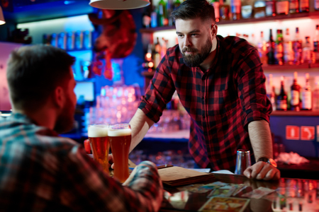 drinks after work: Barman communicating woith his guest at bar Stock Photo