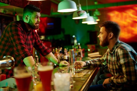 drinks after work: Man resting at bar and communicating with bartender