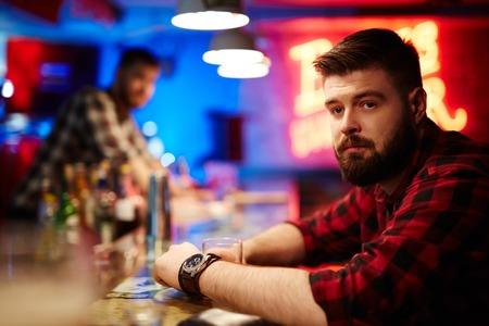 drinks after work: Young man sitting at bar after hard work day