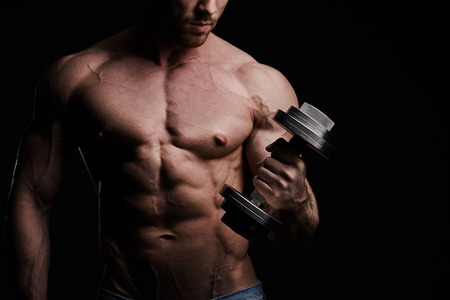 fitness hombres: Tipo culturista muscular que hace ejercicios con pesas sobre fondo negro