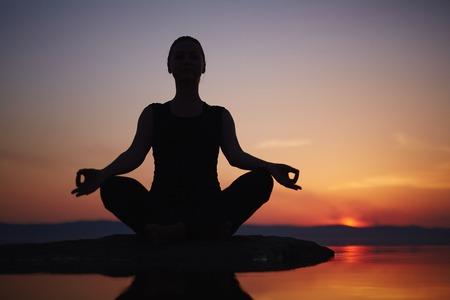 mujer meditando: Mujer meditando cerca del lago Foto de archivo