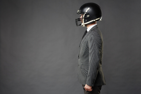 tailored: Sideview of businessman wearing tailored suit and American football helmet standing confidently facing left, isolated on black background.