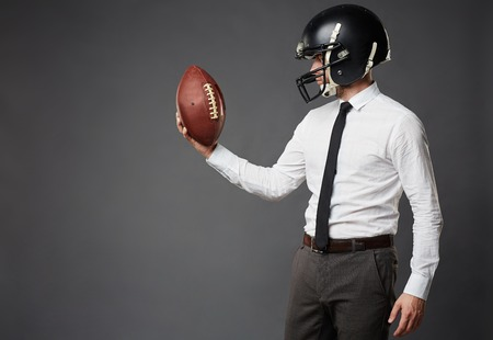 plan: Sideview of businessman in formal clothes and football helmet standing isolated on black background looking in determination at American football.