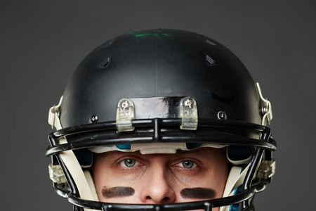 decisive: Isolated on black background closeup of head of blue-eyed man with eye black wearing football helmet and looking at camera prepared to face a challenge.