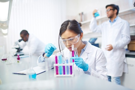 analyses: Concentrated female Asian scientist in lab coat and safety goggles working with colored test tubes in laboratory. Two colleagues in background.