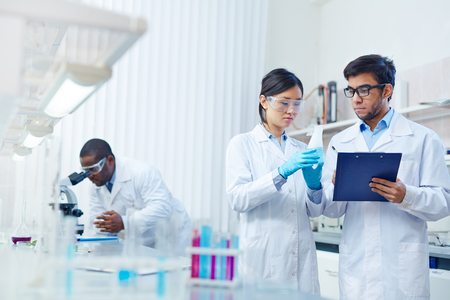 analyses: Concentrated Asian female laboratory scientist in safety goggles holding flask with blue liquid showing it to Latin-American colleague writing down results. African-American scientist in background. Stock Photo