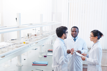High angle shot of pleased male African-American, male Latin-American and female Asian laboratory scientists in lab coats and glasses discussing scientific research.