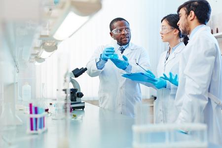 Mannelijke Afro-Amerikaanse laboratorium wetenschapper met kolf met blauwe vloeistof bespreken chemische reactie met mannelijke Latijns-Amerikaanse en Aziatische vrouwelijke collega's. Stockfoto