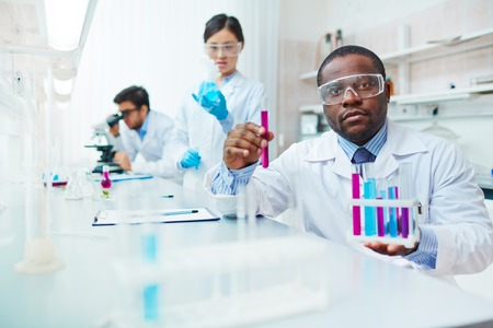 safety goggles: Waist up of male African-American scientist in lab coat and safety goggles looking at camera holding test tubes, female Asian colleague examining flask, male Latin-American scientist in background.