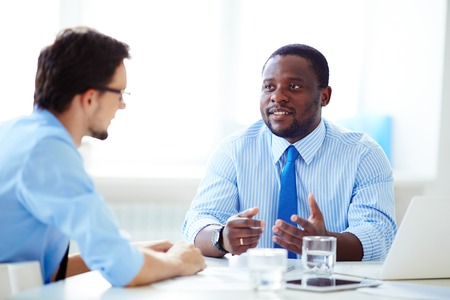 executive assistants: Shot of African-American businessman in shirt and necktie discussing work with Caucasian colleague in shirt and glasses in office.