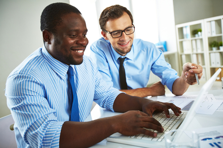 broadly: Broadly smiling African-American businessman in shirt and necktie typing on laptop in office and smiling Caucasian coworker in glasses pointing at laptop screen.