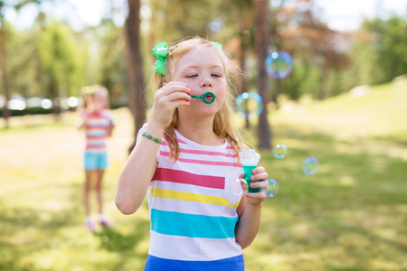 Shot of blond and freckled little girl with ponytails wearing striped t-shirt blowing bubbles in green park on sunny day. Similar girl visible in background.