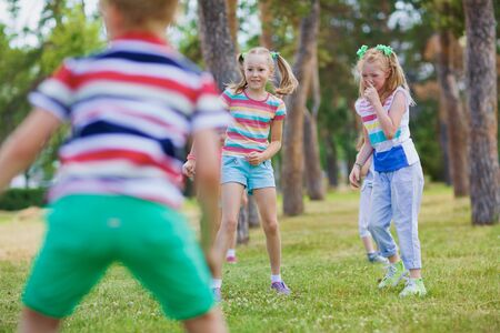 Two blond girls with ponytails in striped t-shirts playing tag in green park on sunny day with their friends. Stock Photo
