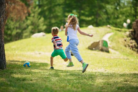 Rear view of blond girl with ponytails and blond boy in striped t-shirt running on green grass towards ball in park on sunny day. Stock Photo