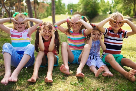 pulling faces: Portrait of four smiling little girls with ponytails and one little blond boy sitting on grass in green park on sunny day holding fingers near eyes like glasses, pulling faces to camera.