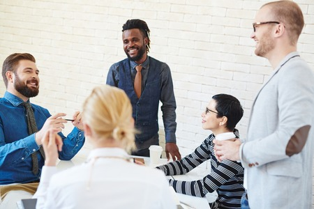 african business man: Group of young business men and women meeting in office, talking and telling stories and jokes at coffee break, African American man standing among them smiling brightly Stock Photo