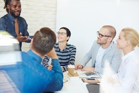 活気のあるカリスマ的なアフリカ系アメリカ人同僚にアイデアを提示を熱心に聞いて事務所に会議用テーブルの幹部のグループ