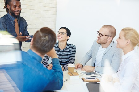 pitching: Group of executives at conference table in office listening intently to lively charismatic Afro-American colleague presenting idea to them