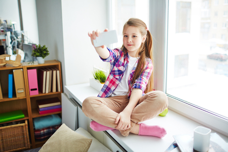 self conceit: Schoolgirl taking selfie with smartphone sitting cross-legged on window sill in her room