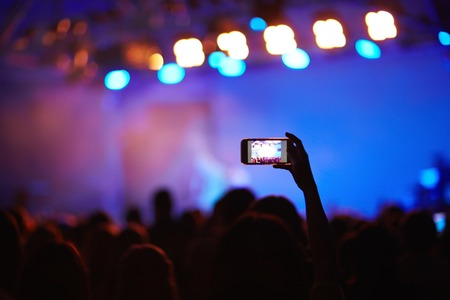 lit image: Back lit image of crowd at music concert before stage, focus on one fan holding cellphone high above heads to take picture of memorable moment