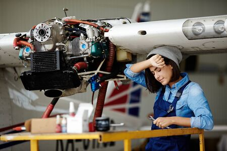 Tired female with wrench standing under air jet part