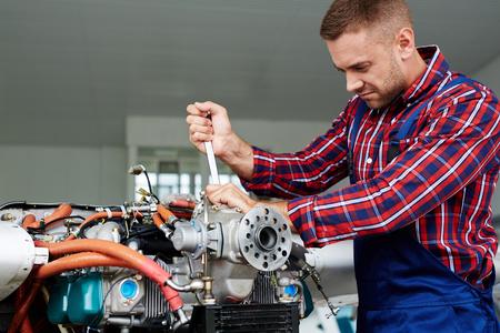 Young mechanic in uniform repairing engine Stock Photo