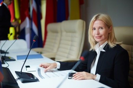 delegar: delegado de sexo femenino que mira a la cámara durante cumbre política