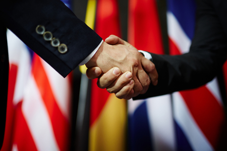 Handshake of two politicians on background of flags