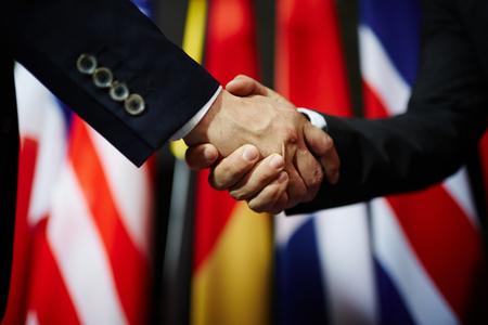 Handshake von zwei Politikern auf den Hintergrund der Flaggen Standard-Bild - 64498505
