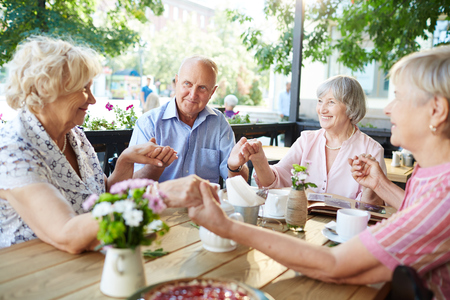 Group of friendly seniors holding by hands by table