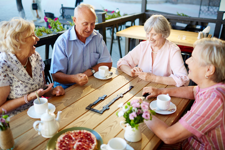 Happy senior friends playing dominoes at leisure